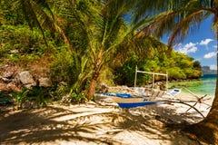 Banca boat at a beautiful tropical beach in Palawan Island,Phili. Traditional banca boat in the shade on the beach near Cudugnon Cave, El Nido, Palawan Island Stock Photography