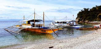 Banca boats sitting on the beach in the early morning awaiting tourists for a day out in the Philippines royalty free stock photo