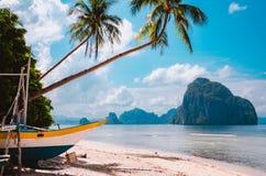 Banca-Boot auf Ufer unter Palmen Szenische Landschaft der Tropeninsel EL-Nido, Palawan lizenzfreie stockfotografie