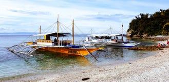 Banca-Boote, die am frühen Morgen auf dem Strand erwartet Touristen während eines freien Tages in den Philippinen sitzen lizenzfreies stockfoto