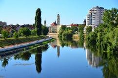 Banca di città riflessa nel fiume. Immagini Stock