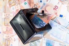 Banca di moneta nera del metallo con soldi Fotografia Stock
