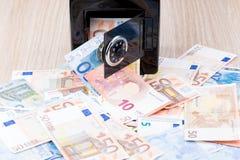 Banca di moneta nera del metallo con soldi Fotografie Stock Libere da Diritti