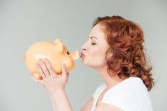 Banca piggy baciante della donna fotografie stock