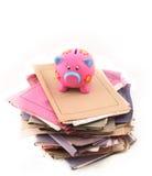 Banca Piggy in cima alla pila di dispositivi di piegatura Immagine Stock Libera da Diritti