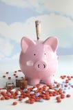 Banca Piggy con le pillole ed i soldi Fotografia Stock