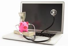 Banca Piggy con lo stetoscopio sul computer portatile Fotografia Stock Libera da Diritti