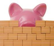 Banca Piggy dietro una parete di mattoni Immagine Stock Libera da Diritti
