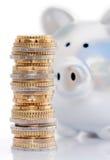 Banca Piggy e pila di soldi Fotografia Stock