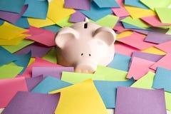 Banca Piggy fino al suo radiatore anteriore nelle note di post-it Fotografia Stock Libera da Diritti