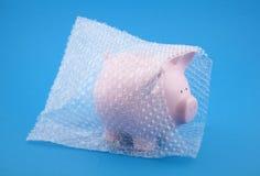 Banca Piggy in involucro di bolla su priorità bassa blu Fotografie Stock Libere da Diritti