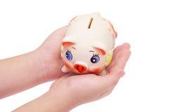Banca Piggy nelle palme della mano del bambino Fotografia Stock