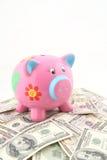 Banca Piggy sopra la pila di soldi Immagine Stock