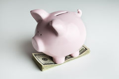 Banca Piggy su una pila di 100 fatture del dollaro Fotografia Stock Libera da Diritti