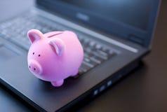Banca Piggy sul computer portatile Fotografia Stock Libera da Diritti