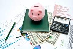 Banca Piggy sulla tabella dell'ufficio Fotografie Stock Libere da Diritti