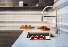 Bancada branca do granito com a decoração do alimento nela e em armários de cozinha de madeira marrons conceito da cozinha Imagens de Stock