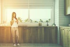 Bancadas de madeira da cozinha sob a janela, mulher Imagens de Stock Royalty Free