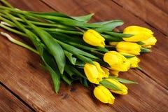 Banch Żółci tulipany kłama na drewnianych deskach Zdjęcie Stock
