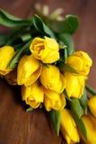Banch Żółci tulipany kłama na drewnianych deskach Obrazy Royalty Free
