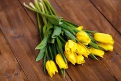 Banch Żółci tulipany kłama na drewnianych deskach Obrazy Stock