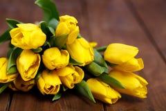 Banch Żółci tulipany kłama na drewnianych deskach Obraz Royalty Free