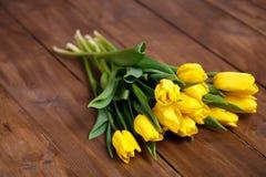 Banch Żółci tulipany kłama na drewnianych deskach Obraz Stock