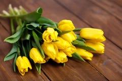 Banch Żółci tulipany kłama na drewnianych deskach Zdjęcie Royalty Free