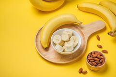 A banch of bananas with almonds on yellow background. A banch of bananas with almonds on yellow background Stock Photos