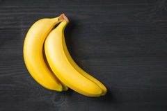 A banch of bananas and a sliced banana in a dish over yellow bac. Kground Royalty Free Stock Images