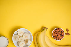 A banch of bananas and a sliced banana in a dish over yellow bac. Kground Royalty Free Stock Photos