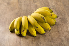 A banch of bananas and a sliced banana in a pot over a table. A banch of bananas and a sliced banana Stock Photography