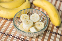 A banch of bananas and a sliced banana in a pot over a wood background Stock Photos