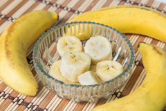 A banch of bananas and a sliced banana in a pot over a wood background Royalty Free Stock Photo