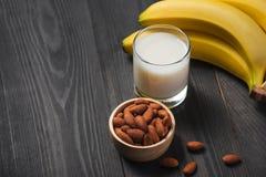 Banch banany z migdałami i mlekiem na drewnianym tle Zdjęcia Royalty Free