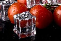 Banch des tomates-cerises et des glaçons rouges sur la table humide noire Se images stock
