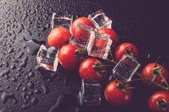 Banch des tomates-cerises et des glaçons rouges sur la table humide noire Se photographie stock libre de droits