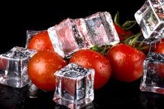 Banch des tomates-cerises et des glaçons rouges sur la table humide noire Se photos stock