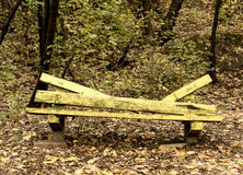 Banch in the park. A  lonely yellow broken bench in park with fallen autumn dry tree leaves Royalty Free Stock Images