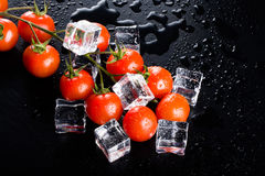Banch of red cherry tomatos and ice cubes on black wet table. Se Stock Photos