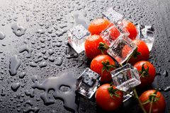 Banch of red cherry tomatos and ice cubes on black wet table. Se Stock Image