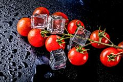 Banch of red cherry tomatos and ice cubes on black wet table. Se Royalty Free Stock Image
