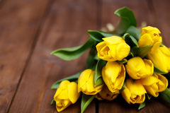 Banch of Yellow tulips lying on wooden boards Stock Photography