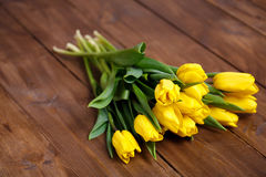 Banch of Yellow tulips lying on wooden boards Stock Image