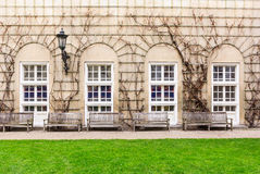 Banchi di legno che affrontano la parete con le finestre di vetro macchiato incurvate nei precedenti Fotografia Stock