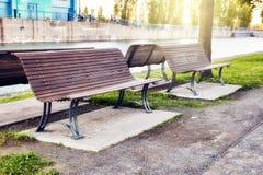 Banchi di legno in un parco vicino alla riva del fiume al tramonto fotografia stock libera da diritti