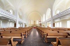 Banchi e croce in cattedrale luterana evangelica Immagine Stock