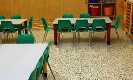 Banchi e piccole sedie verdi in una scuola materna per i bambini Fotografia Stock