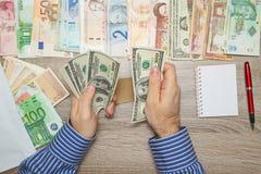 Banchiere che conta i dollari alla sua tavola dell'ufficio, Fotografia Stock Libera da Diritti