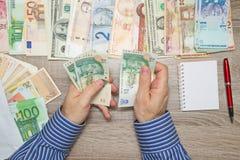 Banchiere che conta soldi sudafricani alla sua tavola dell'ufficio, Immagini Stock